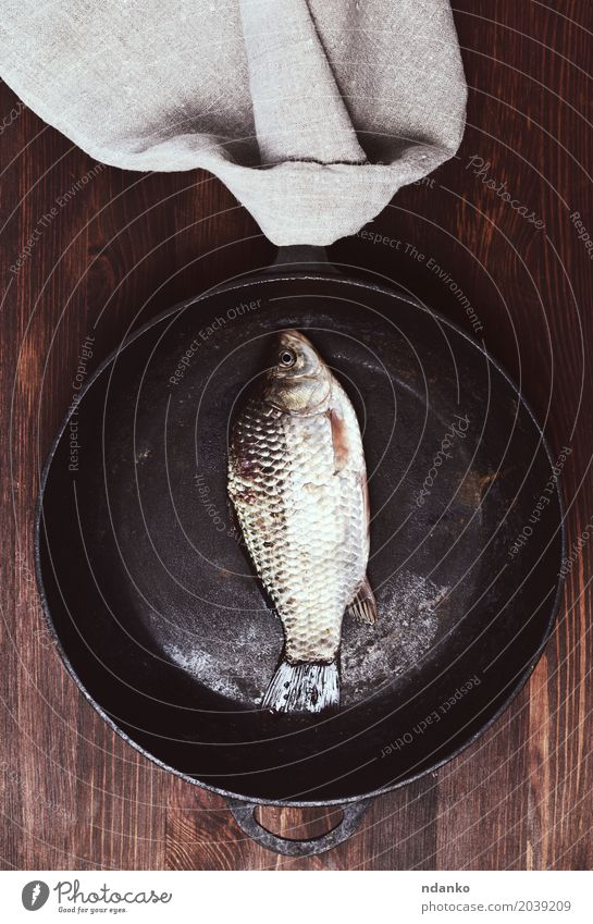 Fresh fish carp in a black frying pan Meat Fish Eating Pan Table Kitchen Wood Natural Above Brown Black Carp whole Gourmet Top Plank healthy cook empty