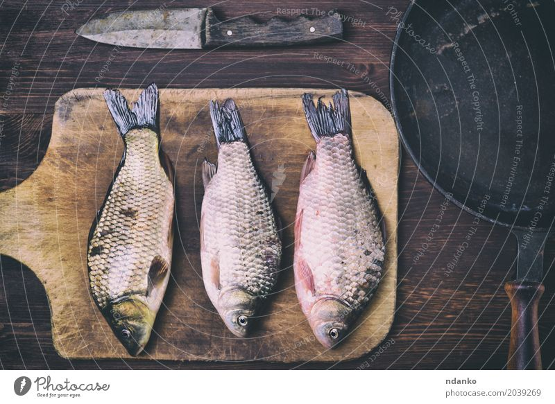 Fish carp on a kitchen cutting board Food Meat Herbs and spices Nutrition Pan Knives Table Kitchen Wood Diet Eating Fresh Delicious Natural Above Brown Black