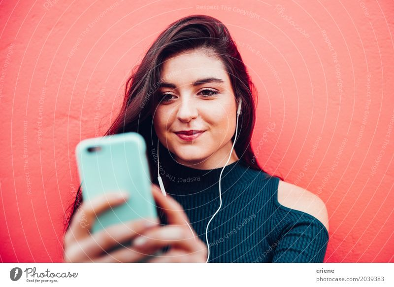 Young caucasian woman listening to music on smart phone Human being Woman Youth (Young adults) Young woman Red Joy Adults Lifestyle Feminine Music Technology Telecommunications Smiling Internet Cellphone Listening