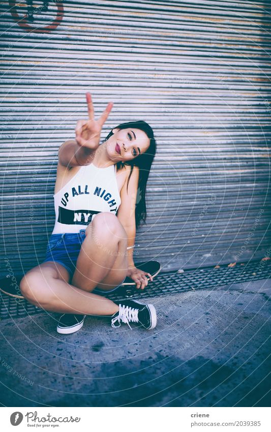 Young happy woman sitting on skateboard making peace hand sign Human being Woman Youth (Young adults) Young woman Joy 18 - 30 years Adults Life Lifestyle