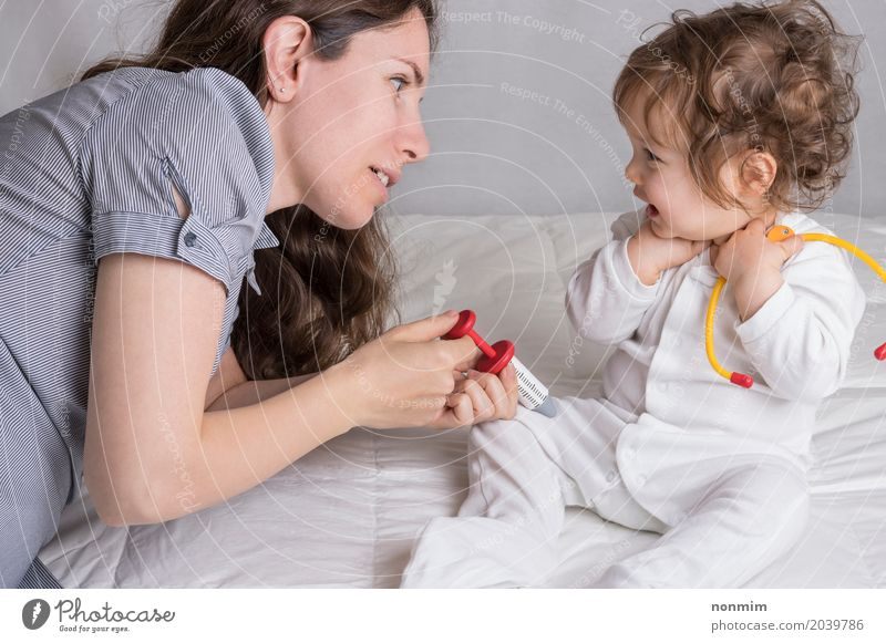 Baby and mom are playing doctor Joy Illness Medication Playing Child Profession Doctor Hospital To talk Toddler Woman Adults Mother Family & Relations Toys