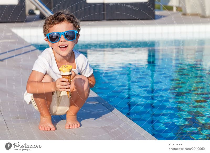 happy little boy with ice cream sitting near a swimming pool Human being Child Nature Vacation & Travel Man Summer Beautiful Sun Relaxation Joy Adults Eating