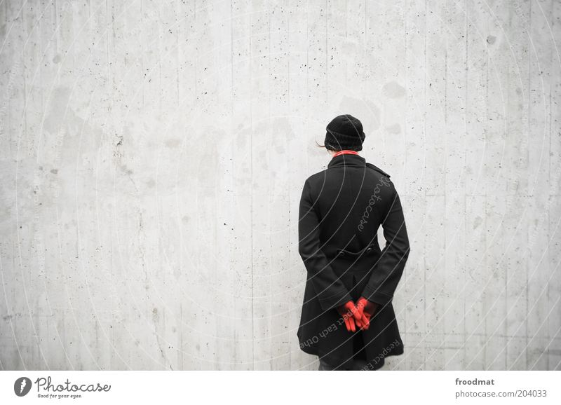 Woman Human being Youth (Young adults) Calm Cold Feminine Wall (building) Wall (barrier) Wait Adults Back Gloomy Stand Cap Coat Shame