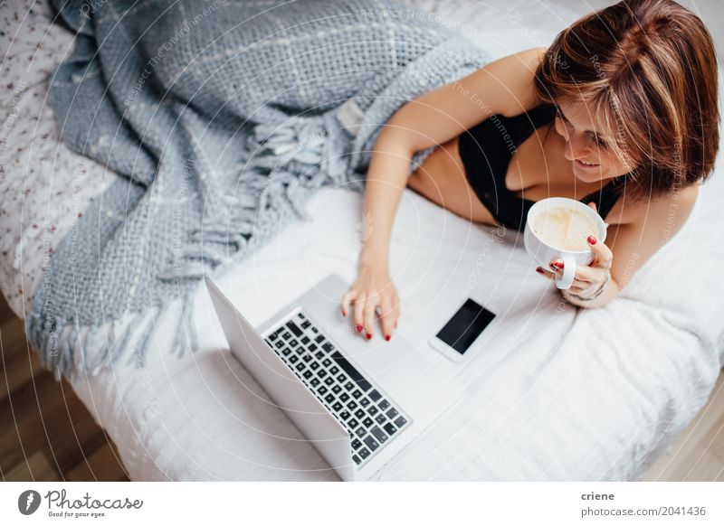 Young caucasian woman drinking coffee in bed with laptop Youth (Young adults) Young woman Lifestyle Feminine Happy Leisure and hobbies Technology Smiling Computer Study Coffee Drinking Internet Home Notebook Online