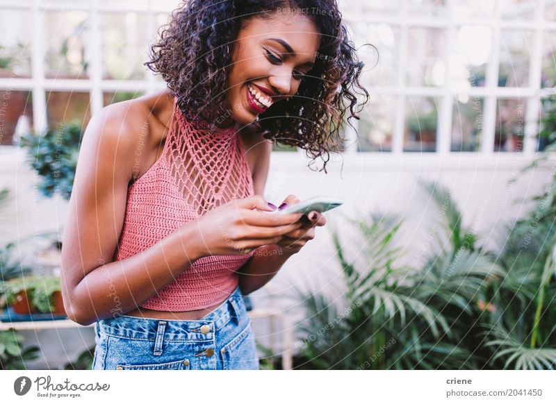 African American happy woman typing message on smartphone Human being Woman Youth (Young adults) Young woman Summer Joy 18 - 30 years Adults Lifestyle Feminine Happy Garden Technology Telecommunications Smiling Telephone