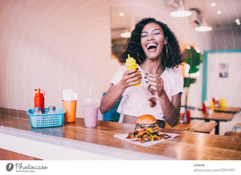 Young happy woman enjoying hamburger and fries in restaurant Youth (Young adults) Young woman Summer Joy 18 - 30 years Adults Eating Lifestyle Sit Smiling