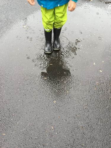 rainy weather Lifestyle Playing Adventure Dance Parenting Child Boy (child) 1 Human being Environment Nature Bad weather Rain Street Protective clothing Boots