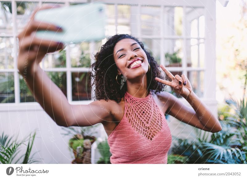 Happy African young woman taking selfie with phone Human being Woman Youth (Young adults) Young woman Summer Joy 18 - 30 years Adults Lifestyle Feminine Garden Technology Smiling Telephone Peace Internet