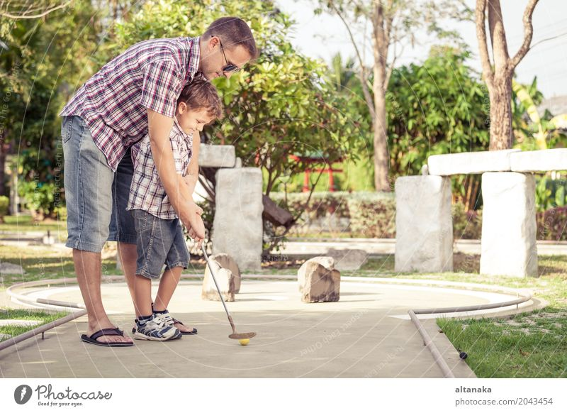 Cheerful young man teaching his son to play mini golf Human being Child Nature Vacation & Travel Man Summer Sun Relaxation Joy Adults Lifestyle Love Sports