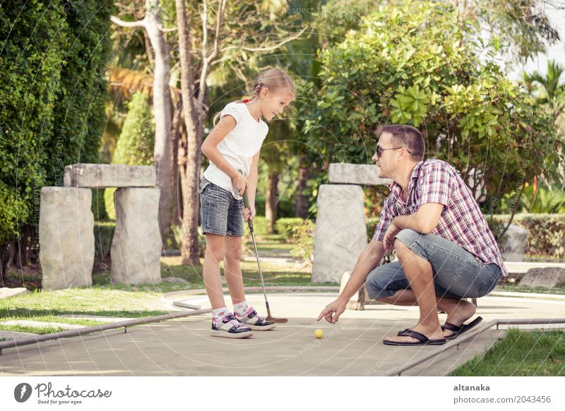 Cheerful young man teaching his daughter to play mini golf Human being Child Nature Vacation & Travel Man Summer Sun Relaxation Joy Adults Lifestyle Love Sports