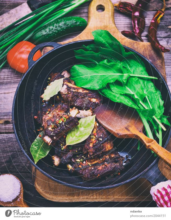 Cooked in spices pork ribs Meat Vegetable Herbs and spices Pan Table Wood Fresh Delicious Green Red Black Pork Ribs Grating Tomato Onion Edible Cooking Salad