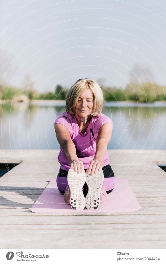 Woman doing yoga by the lake Lifestyle Leisure and hobbies Fitness Sports Training Warming up Yoga Female senior 60 years and older Senior citizen Landscape
