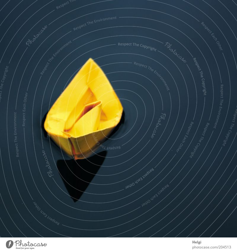 yellow paper boat floating in the water Leisure and hobbies Playing Handicraft Paper Toys Water Esthetic Simple Small Wet Blue Yellow Black Calm Uniqueness