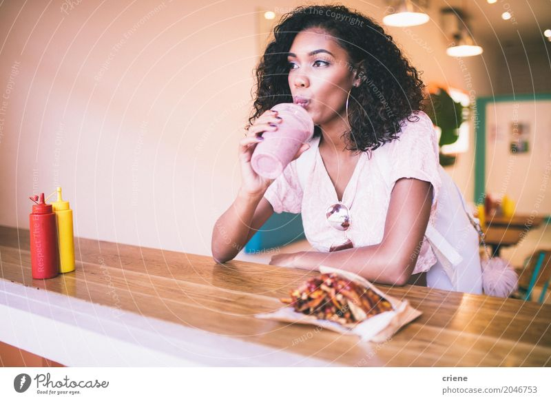 Young Afro American woman having milkshake and fries in bar Human being Woman Youth (Young adults) Young woman Adults Eating Lifestyle Feminine Sit Drinking