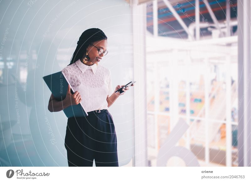 Young Afro American businesswoman using smartphone in office Youth (Young adults) Lifestyle Business Work and employment Office Modern Communicate Technology Success Stand Reading Money Internet Career Notebook PDA