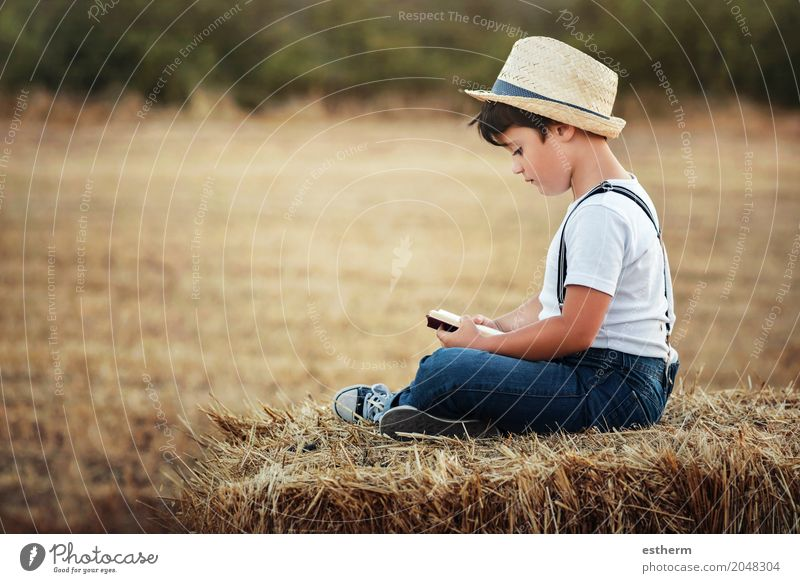 Boy reading a book in the field Lifestyle Leisure and hobbies Parenting Education Child Study Human being Toddler Boy (child) Infancy 1 3 - 8 years Nature