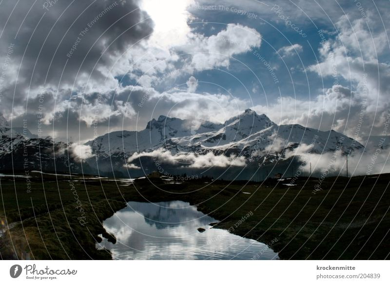alpine ecstasy Nature Landscape Water Sky Clouds Storm clouds Sunrise Sunset Sunlight Winter Bad weather Alps Mountain Peak Snowcapped peak Lakeside Threat Blue