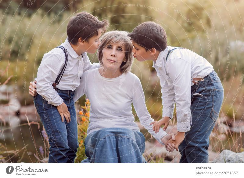 Grandmother with her grandchildren sitting in the field Lifestyle Garden Human being Masculine Feminine Female senior Woman Brothers and sisters Grandparents