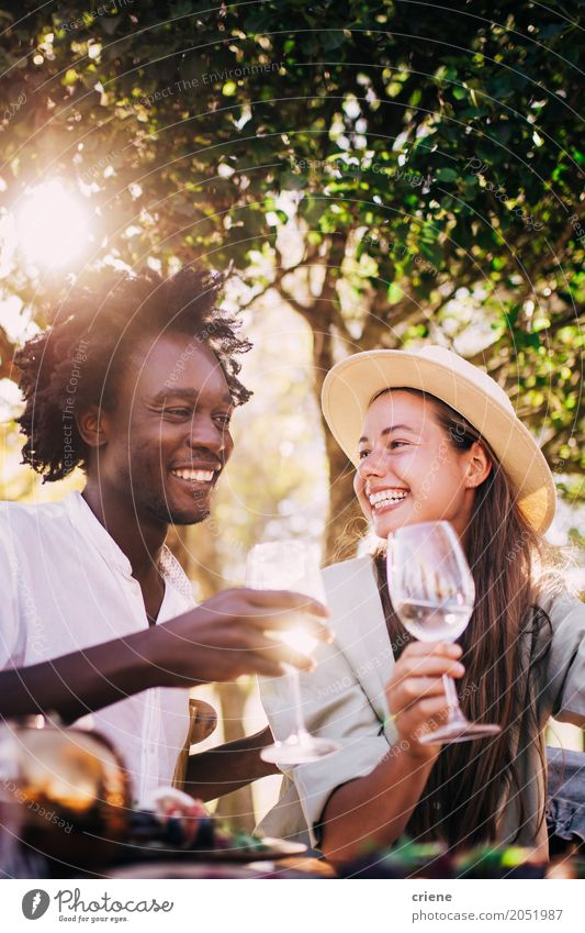 Cute mixed race couple enjoying wine together on date Human being Nature Youth (Young adults) Summer Young woman Young man Tree Joy 18 - 30 years Adults Eating
