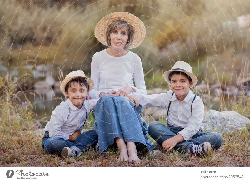 Grandmother with her grandchildren sitting in the field Lifestyle Human being Masculine Feminine Child Toddler Boy (child) Female senior Woman