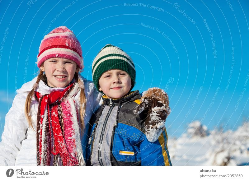 Cute little children playing in snow at a winter day. People having fun outdoors. Concept of Happy new year. Lifestyle Joy Beautiful Face Leisure and hobbies