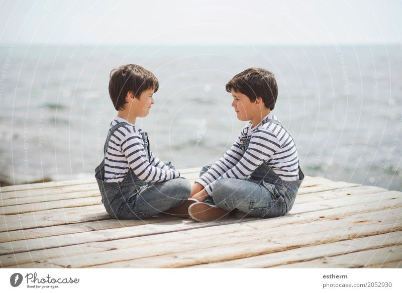 Brothers sitting at waterfront Human being Child Vacation & Travel Joy Beach Lifestyle Love Emotions Boy (child) Family & Relations Together Friendship