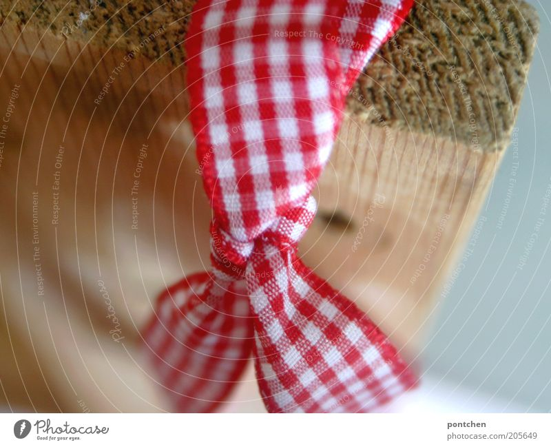 A bow made of red and white checked fabric attached to a wooden board. Gift ribbon. Christmas. Giving Gift wrapping Reddish white Cloth Bow Checkered Adornment