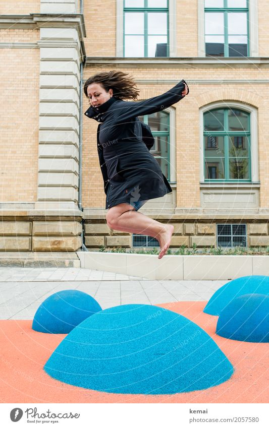 Woman in coat jumps barefoot on blue rubber hills Lifestyle Well-being Contentment Leisure and hobbies Playing Playground Vacation & Travel Freedom City trip