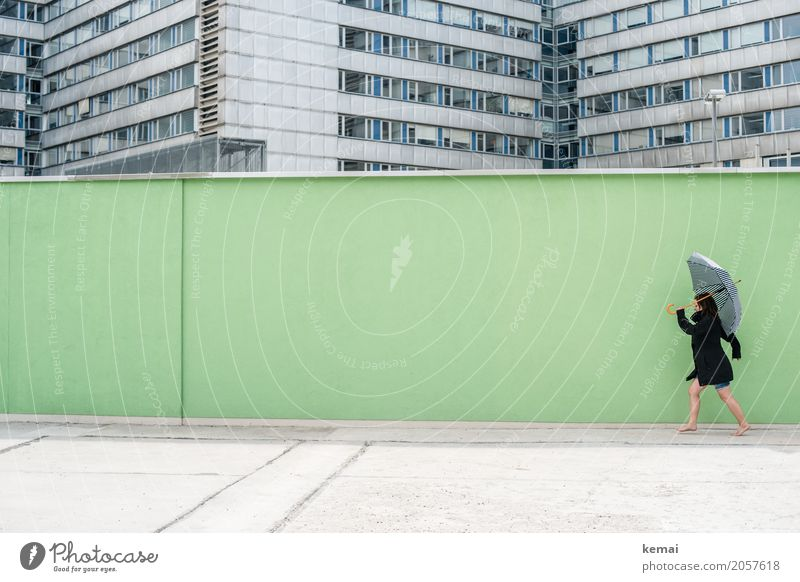 Woman with umbrella in front of a green wall, in the background skyscrapers Style Leisure and hobbies Playing Trip Freedom City trip Wall (building)