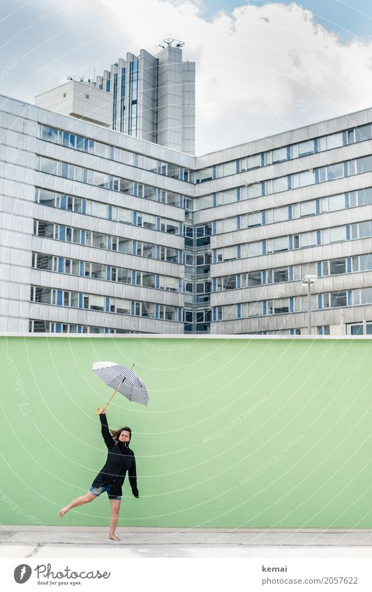 Woman with umbrella in front of a green wall, in the background skyscrapers Lifestyle Well-being Contentment Leisure and hobbies Playing Trip Adventure Freedom