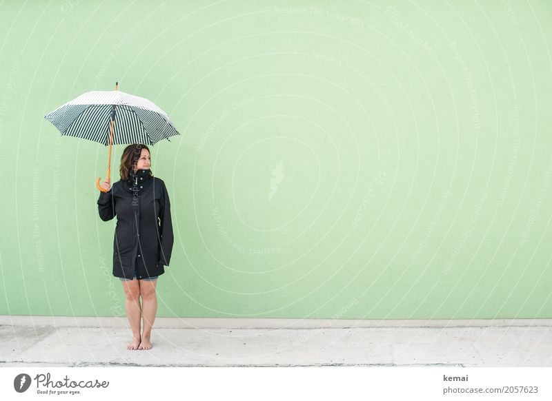 Woman with umbrella in front of green wall Lifestyle Style Harmonious Well-being Contentment Relaxation Calm Leisure and hobbies Vacation & Travel Trip