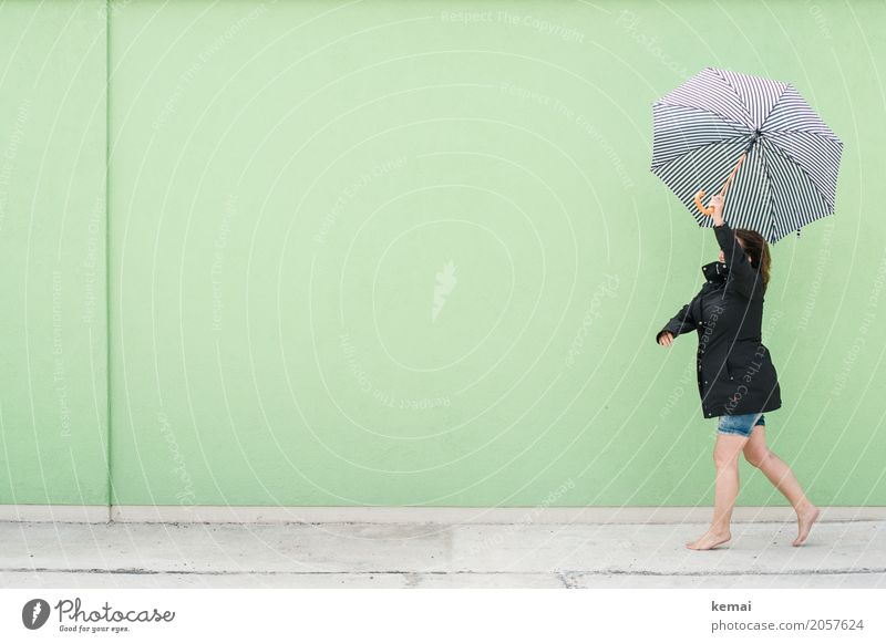 Woman walking with umbrella in front of green wall Lifestyle Style Harmonious Well-being Contentment Leisure and hobbies Playing Trip Freedom Human being