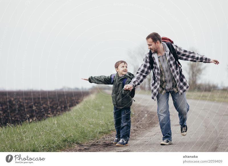 Father and son walking on the road at the day time. People having fun outdoors. Concept of friendly family. Lifestyle Joy Happy Leisure and hobbies