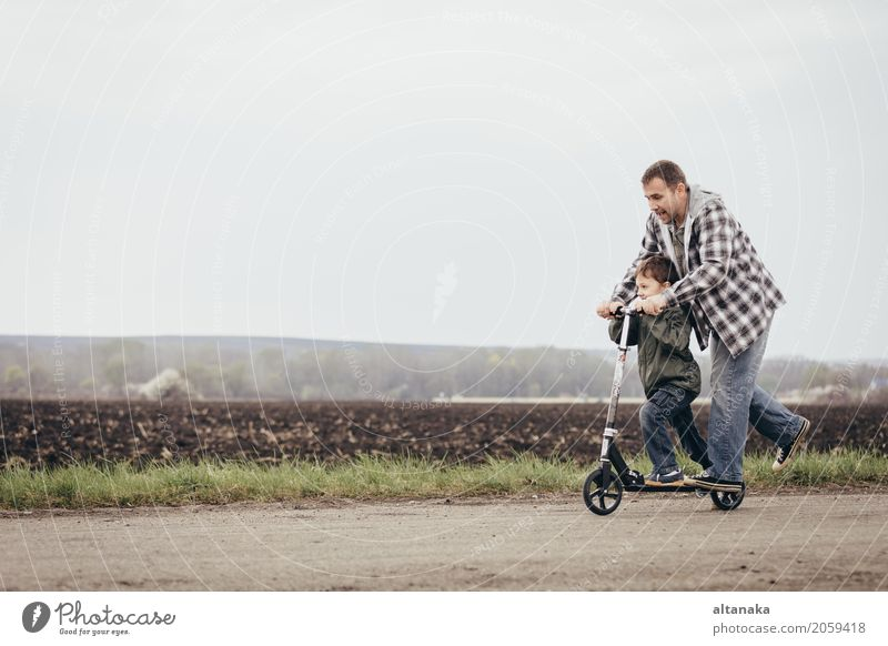 Father and son playing on the road at the day time. People having fun outdoors. Concept of friendly family. Lifestyle Joy Happy Leisure and hobbies Playing