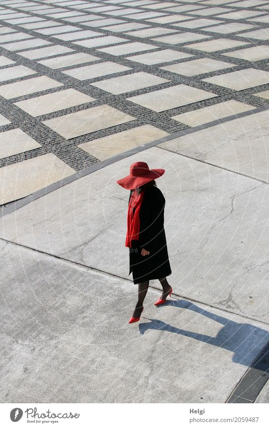 elegantly dressed lady with black coat, red hat, red scarf and red pumps walks on a large square with concrete and patterned floor Human being Feminine Woman