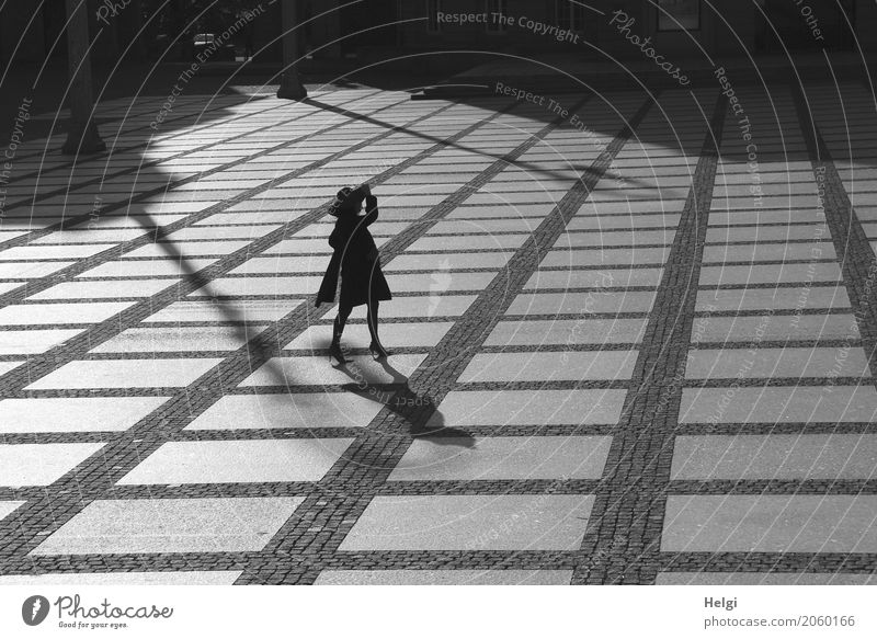 Silhouette of an elegant lady with coat and hat, standing in the back light on a large square with a checkered stone floor Human being Feminine Woman Adults