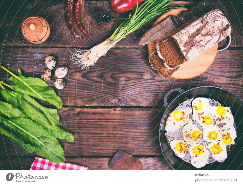 Fried quail eggs Bread Herbs and spices Breakfast Lunch Dinner Pan Knives Kitchen Restaurant Wood Eating Fresh Above Brown Green Red Tradition Onion Dish