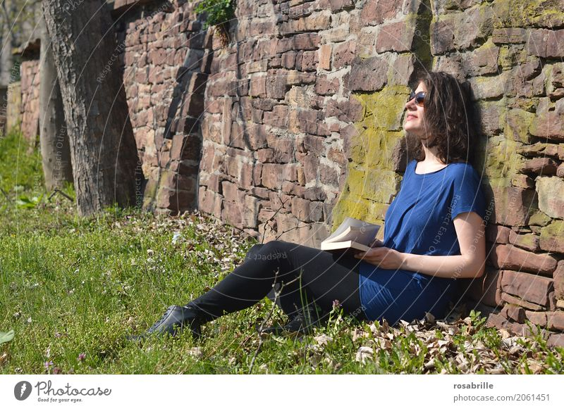 Soaking up the sun - young brunette woman sitting in a park in the grass leaning against a stone wall with a book in her hand and enjoying the sun Human being