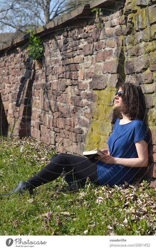 Soaking up the sun - young brunette woman sitting in a park in the grass leaning against a stone wall with a book in her hand and enjoying the sun Well-being