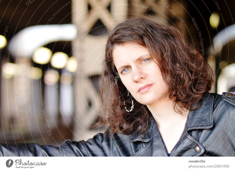 cool young woman with black leather jacket stands in front of steel girders in an underpass and looks confidently into the camera Human being Feminine