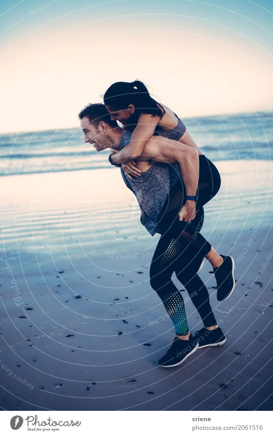 Fit adult couple doing piggyback on beach Lifestyle Joy Personal hygiene Athletic Fitness Beach Ocean Sports Woman Adults Man Couple Partner