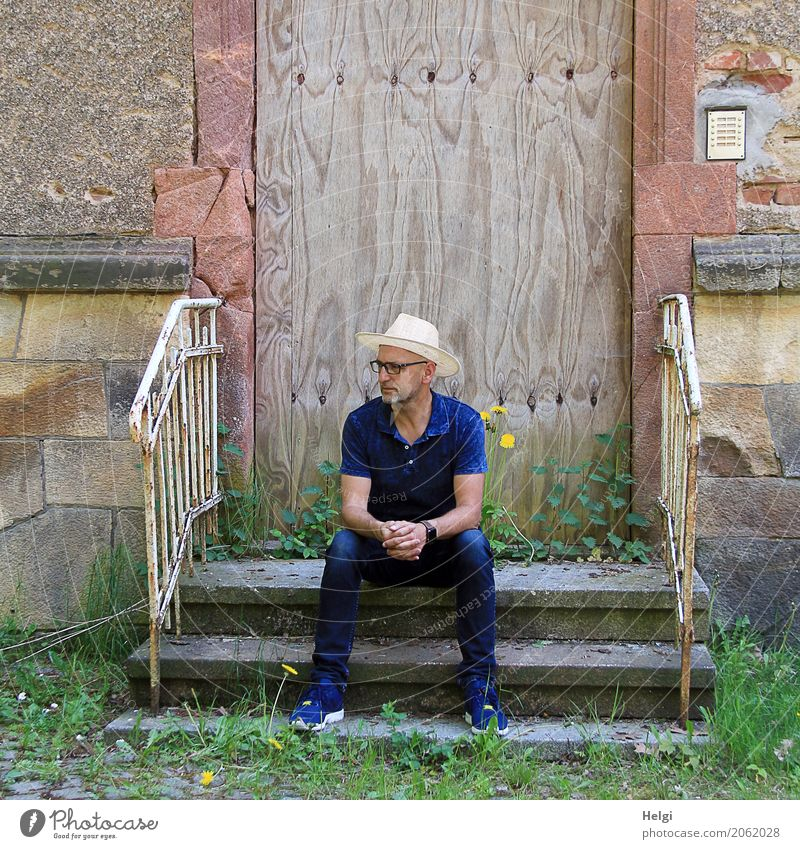 Man with beard, glasses and sun hat in dark blue clothes is sitting thoughtfully on a staircase in front of a dilapidated building Human being Masculine Adults