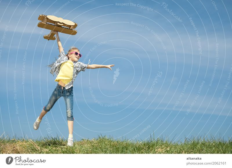 Little girl playing with cardboard toy airplane Human being Child Sky Nature Vacation & Travel Summer Sun Joy Lifestyle Sports Grass Playing Small Happy Freedom