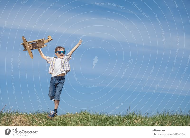 Little boy playing with cardboard toy airplane Human being Child Sky Nature Vacation & Travel Summer Sun Joy Lifestyle Sports Grass Boy (child) Playing Small