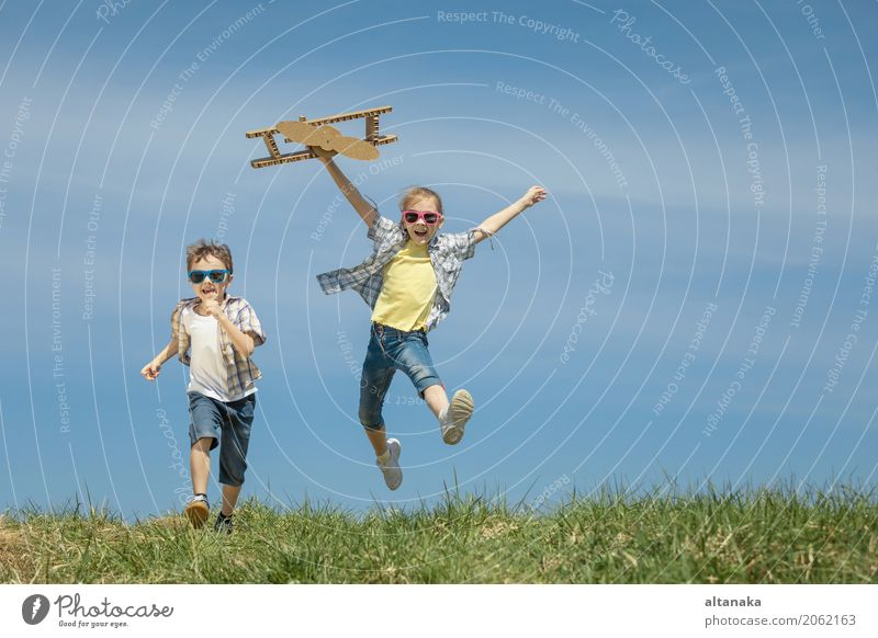 Two little kids playing with cardboard toy airplane Human being Child Nature Vacation & Travel Summer Sun Joy Lifestyle Emotions Sports Grass Boy (child)