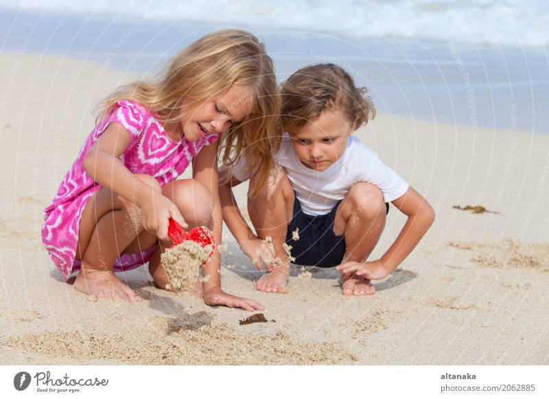 Two happy children playing on the beach Human being Child Nature Vacation & Travel Summer Beautiful Sun Hand Ocean Relaxation Joy Beach Lifestyle Emotions