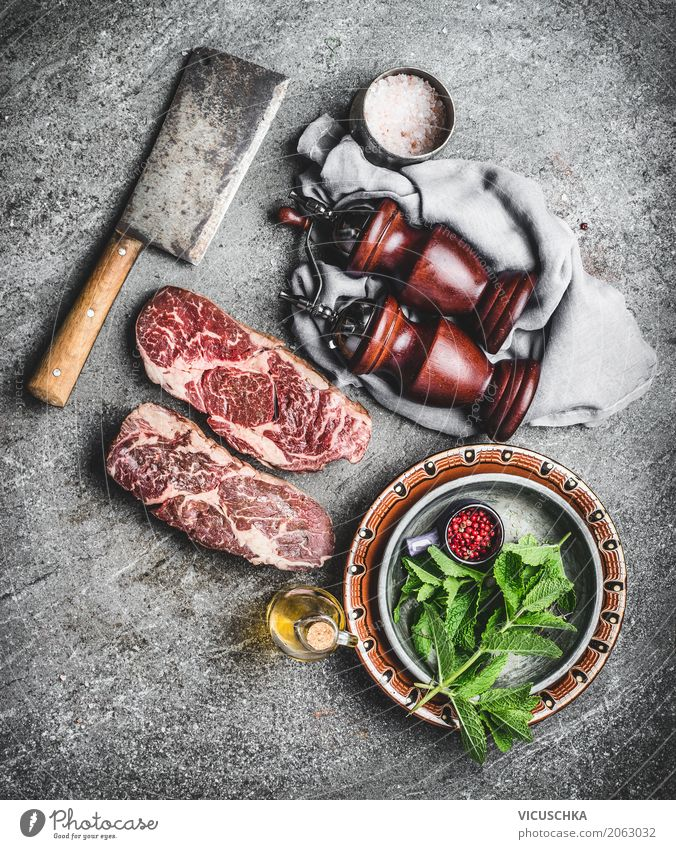 Marbled Ribeye steaks on the kitchen table Food Meat Herbs and spices Nutrition Lunch Dinner Organic produce Crockery Knives Style Design Table Kitchen