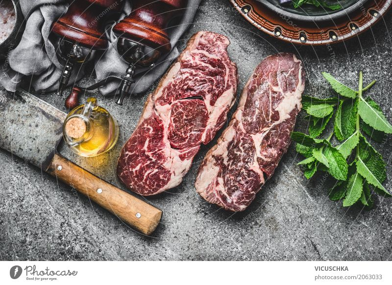 Two marbled raw beef steaks with mincing knife and spices Food Meat Herbs and spices Cooking oil Nutrition Lunch Dinner Picnic Crockery Knives Style Design