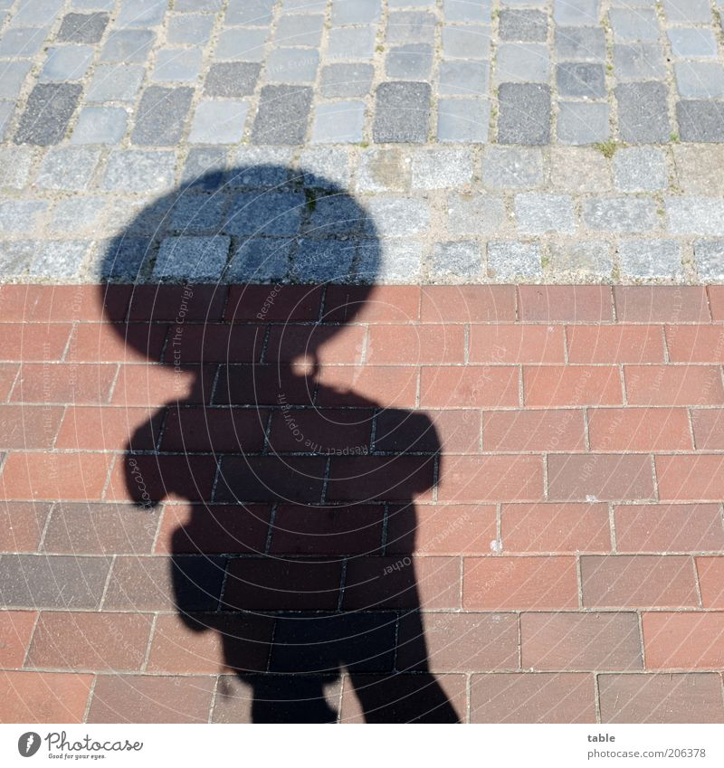 hombre emprendedor Human being Masculine Man Adults 1 Stone Brick Stand Wait Dark Large Gray Red Black Serene Shadow play Sidewalk Colour photo Exterior shot