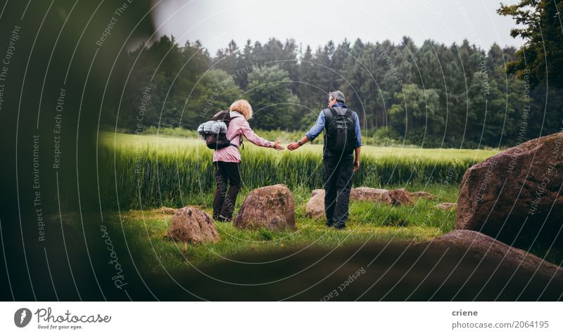 Mature Couple hiking trough green fields Human being Woman Man Joy Forest Adults Life Lifestyle Love Senior citizen Sports Together Leisure and hobbies Hiking